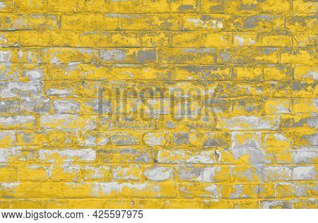 Old Grunge Weathered Gray Concrete Brick Wall With Scaling Yellow Paint Flakes, Stains And Defects