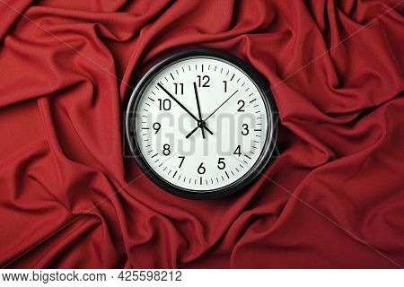 Close Up White Wall Classic Clock Over Red Textile Background With Folded Pleats Of Fabric, Elevated