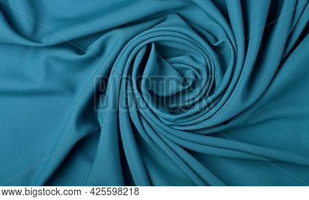 Close Up Abstract Textile Background Of Spiral Shaped Pastel Blue Folded Pleats Of Fabric, Elevated