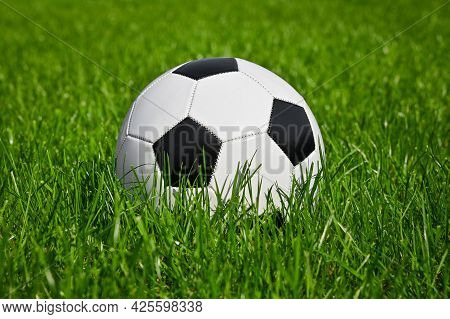 Close Up One Black And White Football Ball In Green Grass Of Soccer Turf Field Pitch, Low Angle, Sid