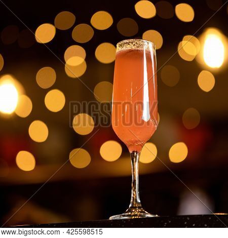 Luxury Alcoholic Drink. Tall Wine Glass With Orange Beverage On Black Background With Backlit Bokeh.