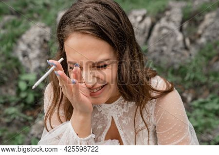 A Cheerful Young Woman With A Cigarette Laughs And Smokes. Harmful Habit.