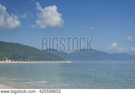 A Pier Leading Out In The Malacca Strait And  Mountains Along The Coast Of Penang Malaysia At Long B