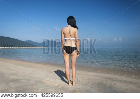 A Chinese Woman Wearing A White And Black Bikini Looking Out At The Malacca Straits At Long Beacn Ba