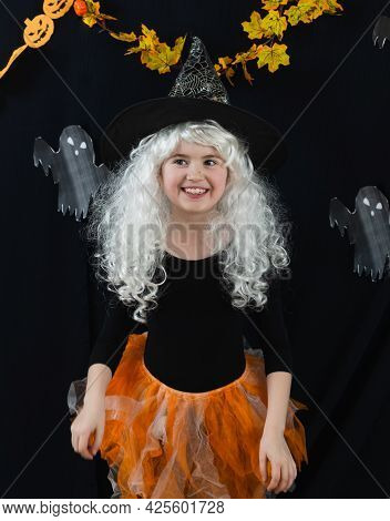 A Cheerful Girl In A White Wig And A Witch Costume On A Black Background With Ghosts. Funny Horror