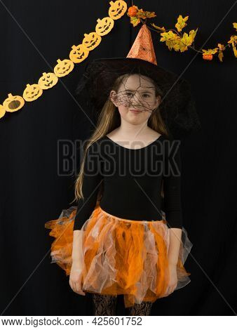 A Cheerful Girl Is Standing In A Witch Costume For A Halloween Celebration. Orange Hat And Skirt, Bl
