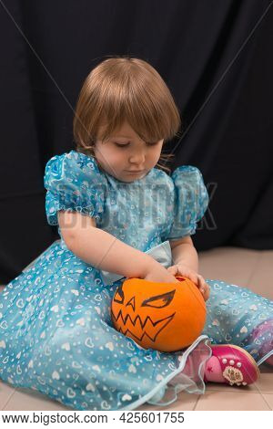 A Cheerful Toddler Girl In A Beautiful Blue Dress Takes Out Candy From A Pumpkin. Jack-o-lantern