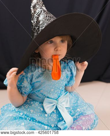 A Cheerful Toddler Girl In A Beautiful Blue Dress With An Orange Balloon And A Black Witch Hat
