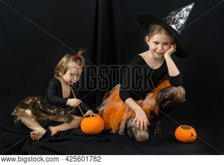 Two Sisters In Witch Costumes. The Younger Girl Cooks A Magic Potion In A Bucket-pumpkin, The Older