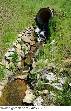 From A Large Concrete Pipe In The Hill, A Spring With Water Flows Out And Flows Along A Specially La