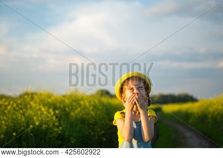Girl In Yellow Blooming Field Covered Her Nose And Face With Hands And Wrinkled Up - An Unpleasant S