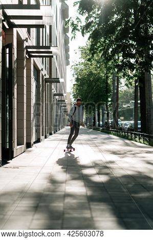 Young Casual Man On Longboard Riding City Street. Millennial Hipster Guy Student Longboarder Skatebo