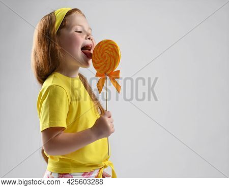 Side View Of A Smiling Little Red-haired Girl In A Summer Fashionable Outfit Licking Lollipops. Stud