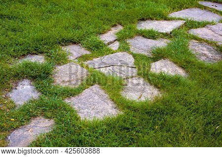 Landscaped Garden Path Made Of Natural Rough Stone Overgrown With Grass On A Summer Green Lawn In Th