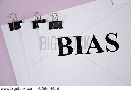 Handwriting Text Bias Written On White Piece Of Paper And Pink Background