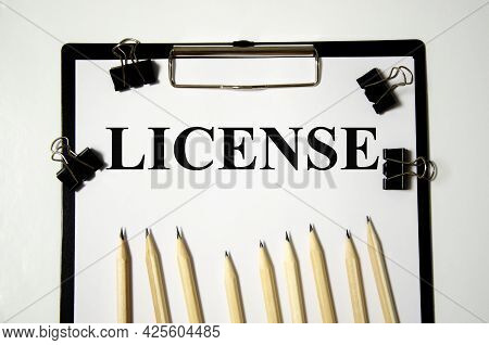 License Word The Word Is Written On A White Piece Of Paper With Pencils