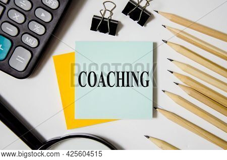 Coaching Text Written On A White Notepad With Colored Pencils And A Yellow Background. Word Business