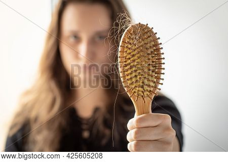 Young Woman Holding A Comb With A Lock Of Hair In Front Of Her, Focus On Comb, Hair Loss Problem, A