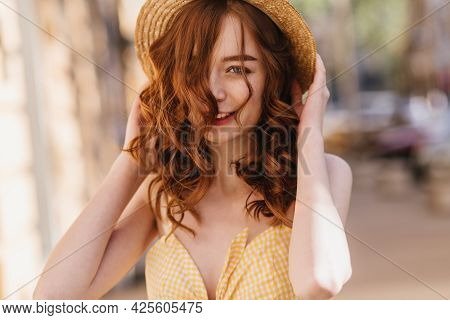 Good-humoured Ginger Girl In Yellow Clothes Posing On Blur Street Background. Refined Red-haired Wom