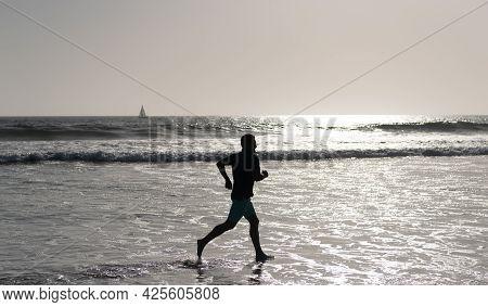 Athletic Man Runner Silhouette Run On Summer Beach With Sea Water And Sun, Endurance