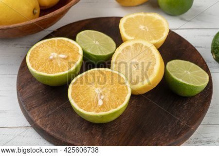 Orange, Green Lemon And Sicilian Lemon Cuts Over Wooden Board.