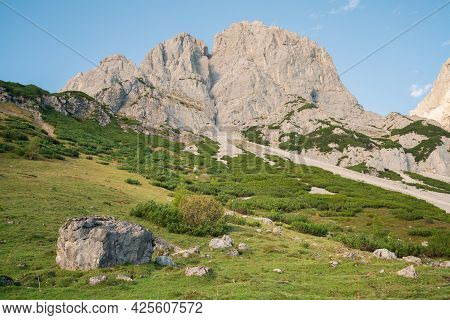 Late Afternoon Under Rocky Cliff In Austrian Alps With Alpine Meadow Below.