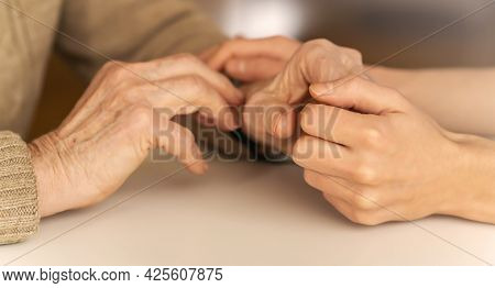Young Womans Hands Hold Grandmothers Hands, An Elderly Patient. Handshake, Caring, Trust And Support
