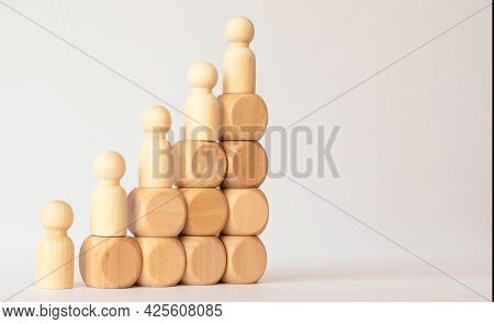 A Wooden Toy Woman Stands On A High Pyramid Stairs And Looks Out At A Large Number Of People Who Obe