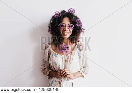 Laughing African Girl With Black Hair Posing With Purple Flowers. Studio Shot Of Enchanting Curly La