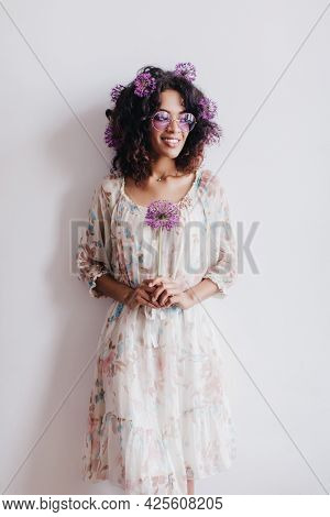 Wonderful Black Female Model Standing In Front Of White Wall With Flower. Happy African Lady Holding