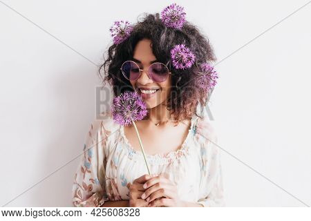 Charming Female Model With Dark Skin Holding Allium And Expressing Happiness. Indoor Photo Of Good-l