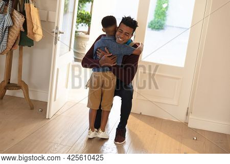 Happy african american father with son back from work smiling and embracing at home. family enjoying quality free time together.