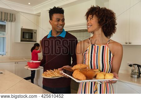 Happy african american couple preparing food in kitchen for breakfast for family and smiling. family enjoying quality free time together.