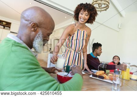 Happy african american multi generation family sitting at table during breakfast and smiling. family enjoying quality free time together.