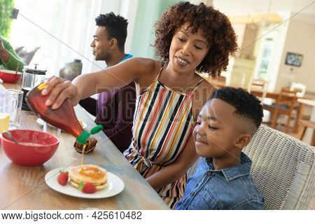 Happy african american family sitting at table smiling during breakfast. family enjoying quality free time together.