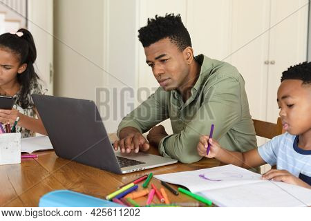 Happy african american father using laptop, daughter and son doing homework at home. family domestic life, spending time learning together at home.