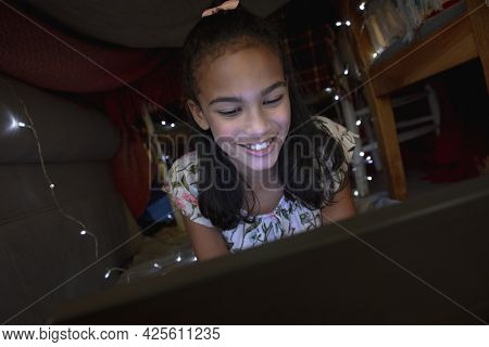Happy african american girl at home, lying in blanket fort and using tablet. childhood with technology, spending free time at home.