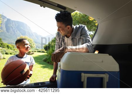 Happy african american father with son outdoors, preparing for picnic on sunny day. family enjoying quality free time together.