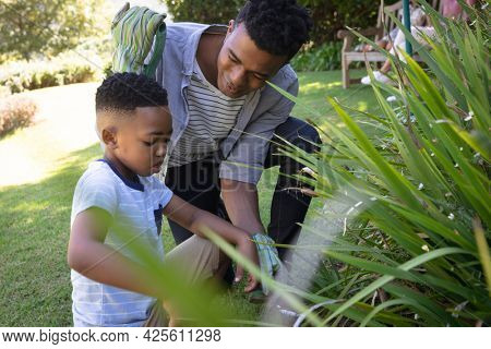 Happy african american father with son outdoors, gardening on sunny day. family enjoying quality free time together.