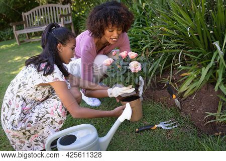 Happy african american mother with daughter outdoors, gardening on sunny day. family enjoying quality free time together.