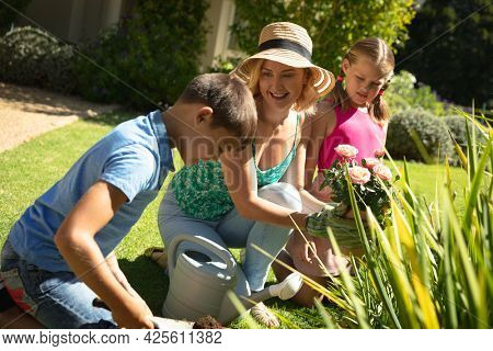 Happy caucasian mother with son and daughter outdoors, gardening on sunny day. family enjoying quality free time together.