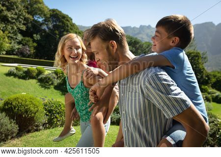 Happy caucasian couple with daughter and son outdoors, playing in sunny garden. family enjoying quality free time together.