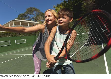 Caucasian mother and son outdoors, playing tennis on tennis court. family enjoying healthy free time activities together.