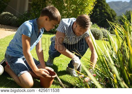 Happy caucasian father and son outdoors, gardening on sunny day. family enjoying quality free time together.