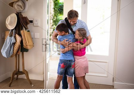 Happy caucasian father with son and daughter at home, smiling and embracing. family enjoying quality free time together.