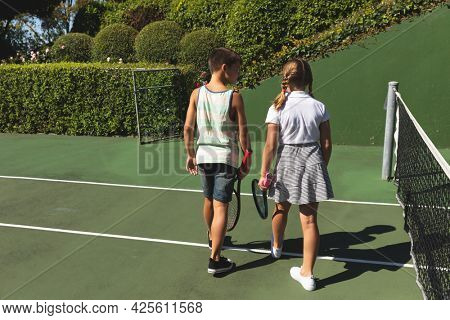 Caucasian boy and girl outdoors, holding tennis rackets and walking on tennis court. family enjoying healthy free time activities together.