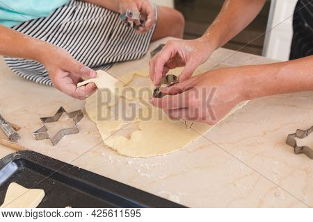 Caucasian mother and daughter baking together in kitchen, cutting cookies. family enjoying quality free time preparing food together.