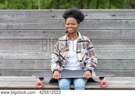 Happy Smiling African Woman In Casual Wear And Trendy Earnings Hold Longboard. Active Afro American