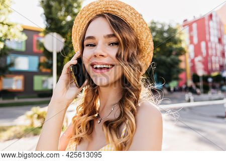 Good-humoured White Girl Talking On Phone In Summer Day. Outdoor Portrait Of Spectacular Lady In Hat