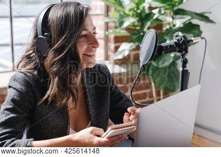 Female radio host broadcasting online in a studio